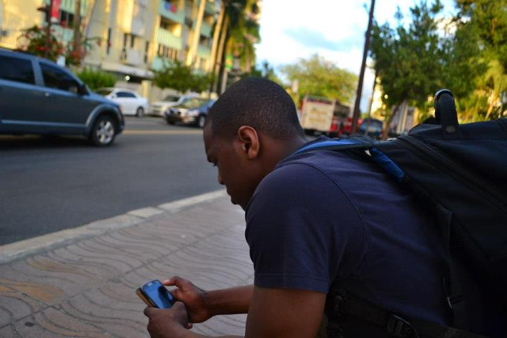 guy looking at his phone on the street