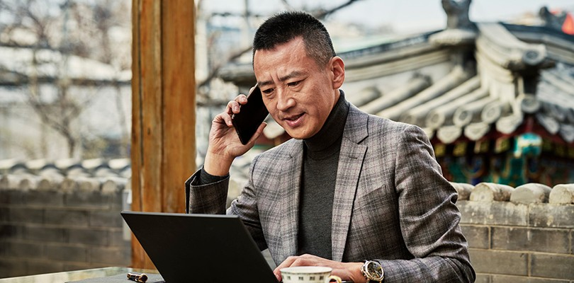 Man on the phone working outside with laptop