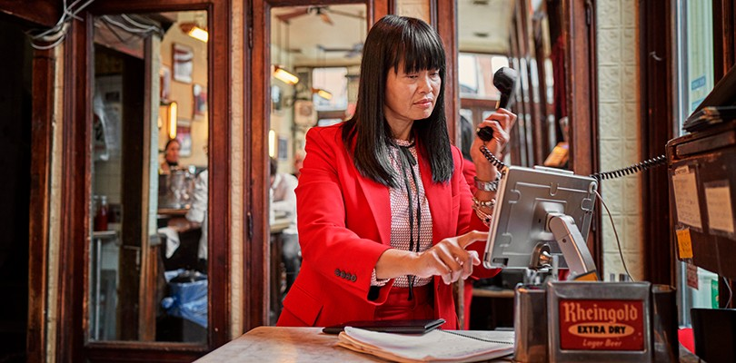 Woman managing a front of house system in a restaurant.