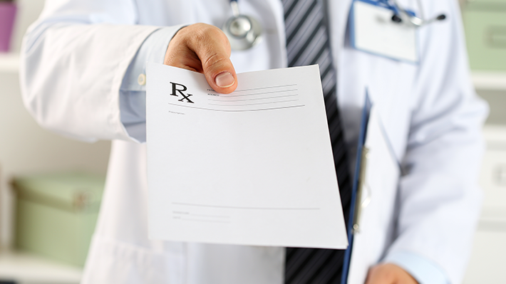Doctor in Lab Coat Holds Out Prescription Pad