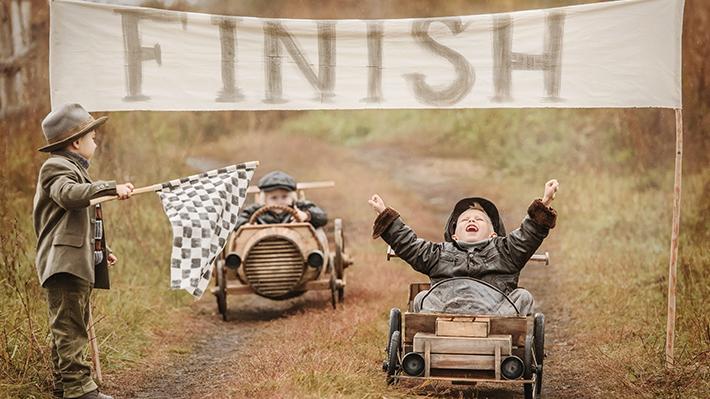 Boy Crossing Finish Line in Homemade Racecar