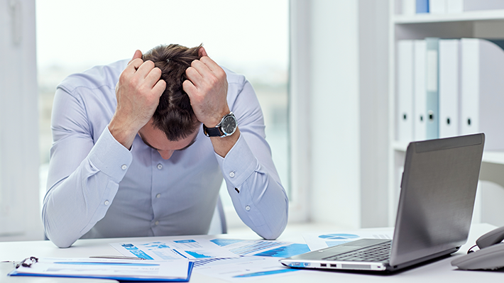 Businessman Holding Head in Frustration