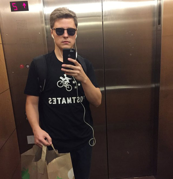 Selfie photo of Lukas Yla in Postmates t-shirt, sunglasses, and carrying grocery bag in elevator