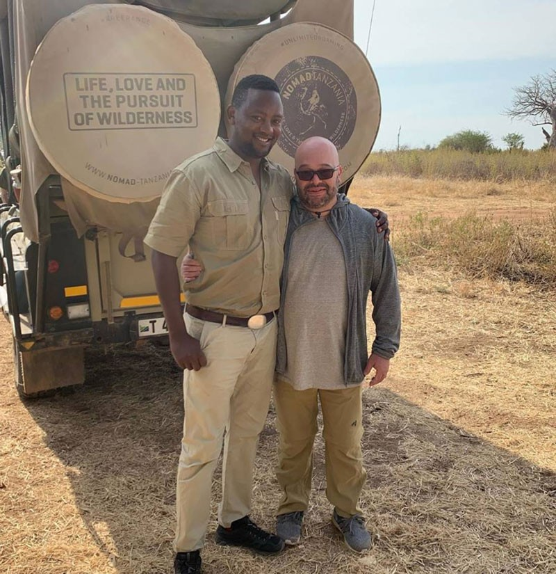 Photo of Ed Nathanson with safari guide Rajabu Hussein, in front of a jeep in Tanzania.