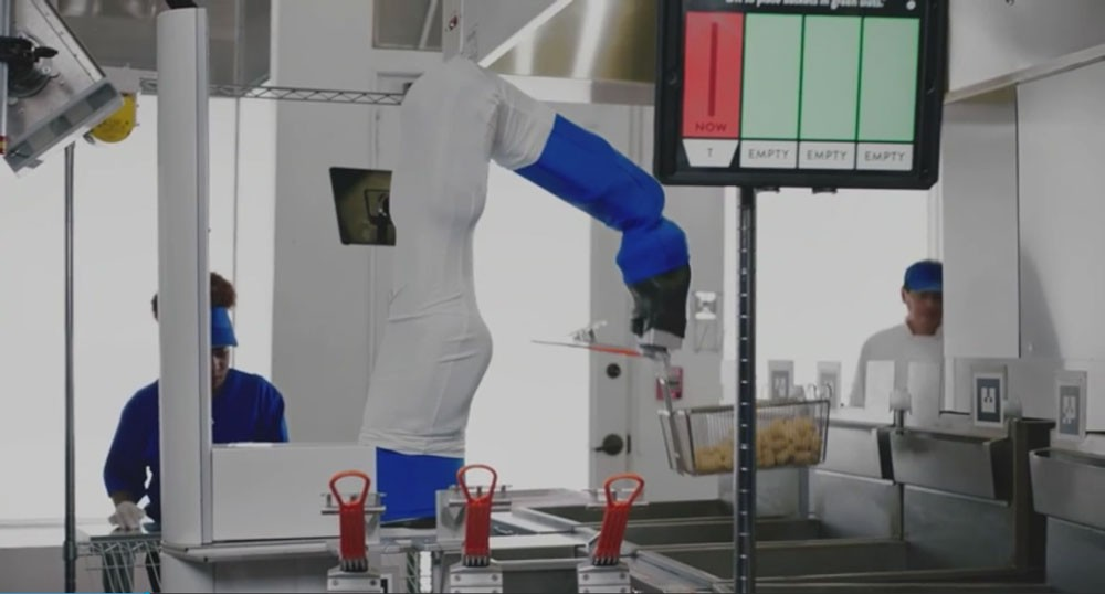 Screenshot from HBO Vice documentary of robot arm working the fryer in a fast food kitchen.