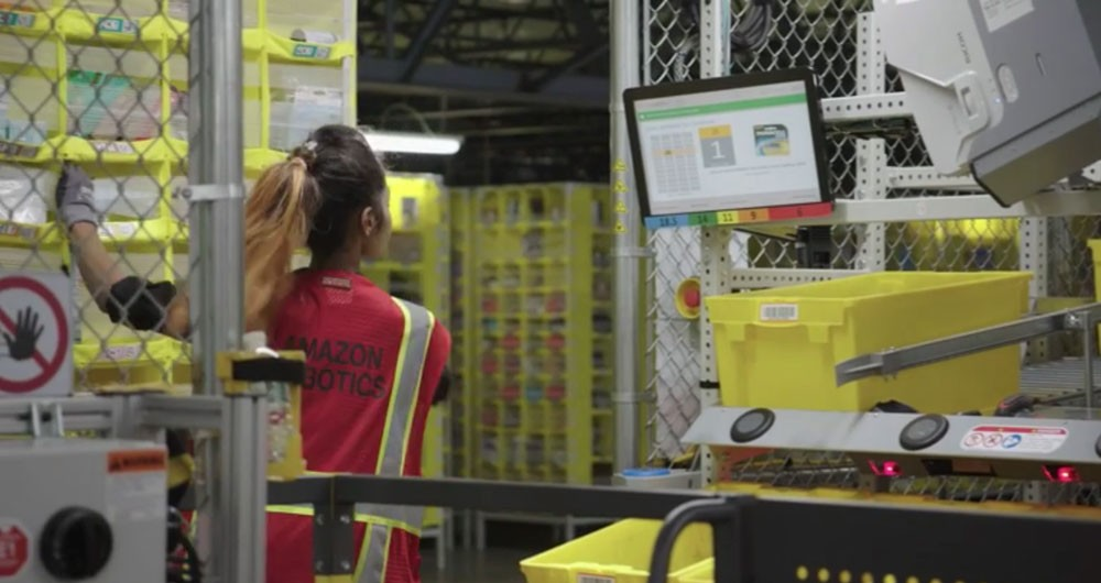 Screenshot from HBO Vice documentary of an employee working with robotics in one of Amazon's fulfillment centers.