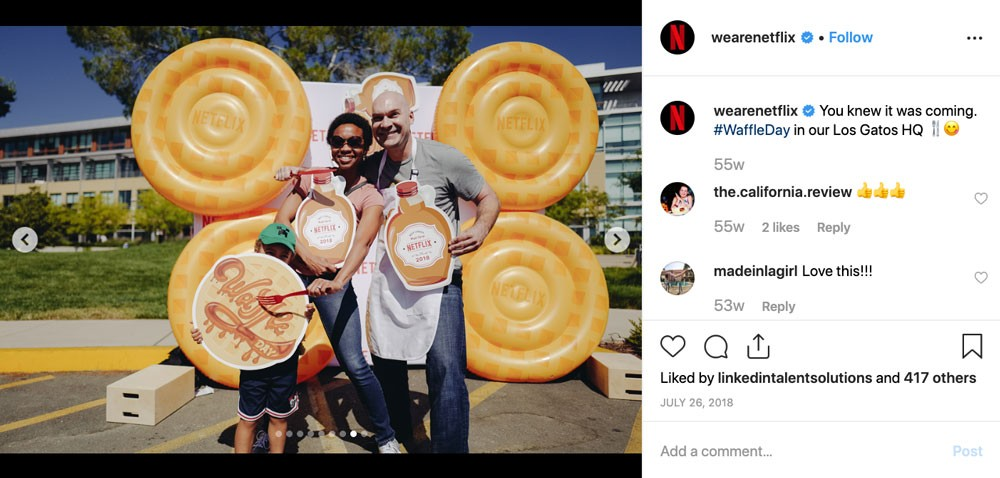 "Screenshot of Netflix's WeAreNetflix Instagram account.  Photo shows a family posing with cardboard cutouts of waffles and syrup bottles.  Caption reads: ""You knew it was coming. #WaffleDay in our Los Gatos HQ."""
