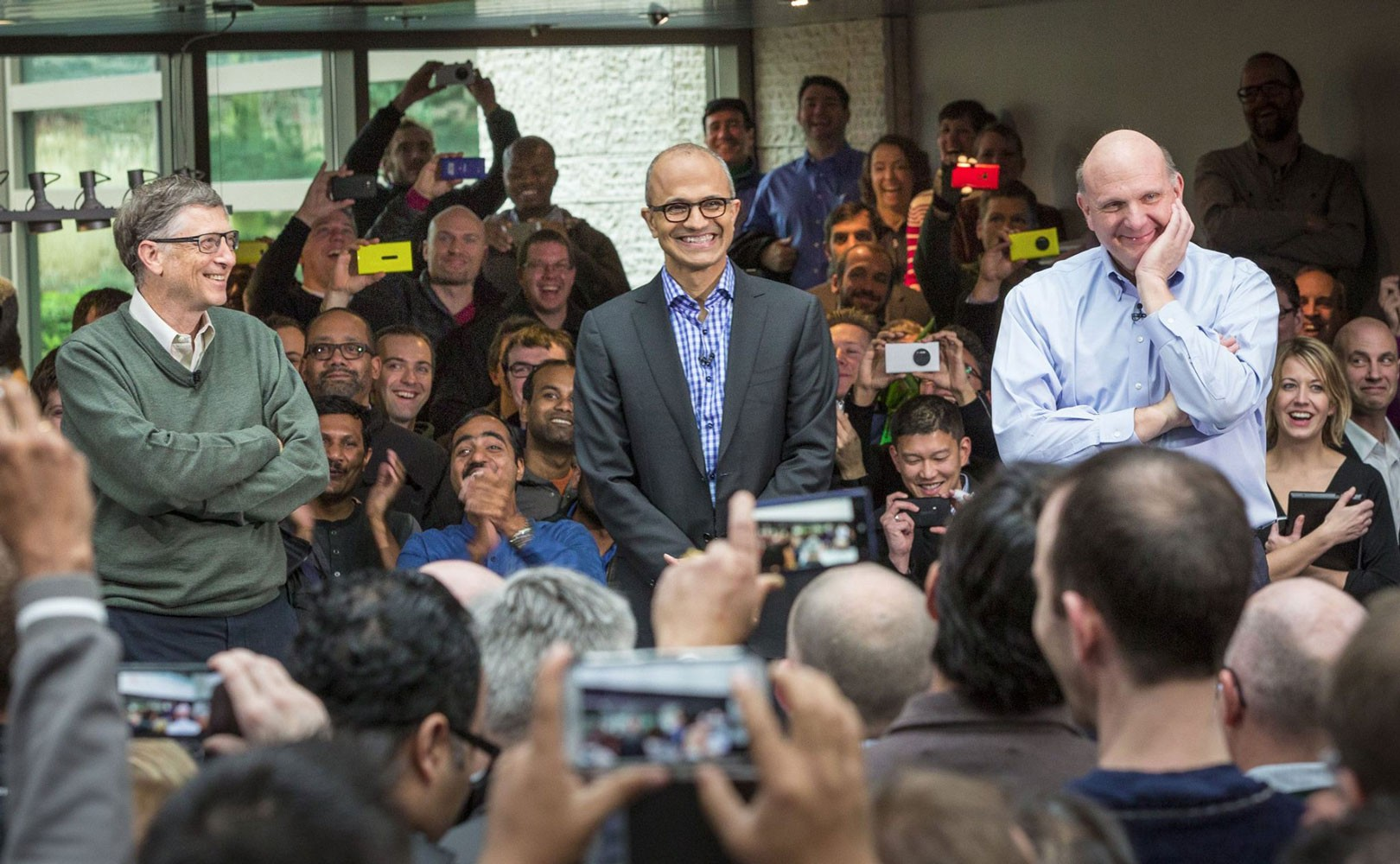 Photo of Microsoft employees gathered around Bill Gates and CEO Satya Nadella at employee rally