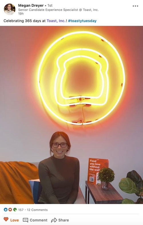 Screenshot of Megan Dreyer, Toast's Senior Candidate Experience Specialist, on her LinkedIn page  Social copy: Celebration 365 days at Toast, Inc! #toastytuesday  Photo is of Megan sitting beneath neon sign of Toast logo