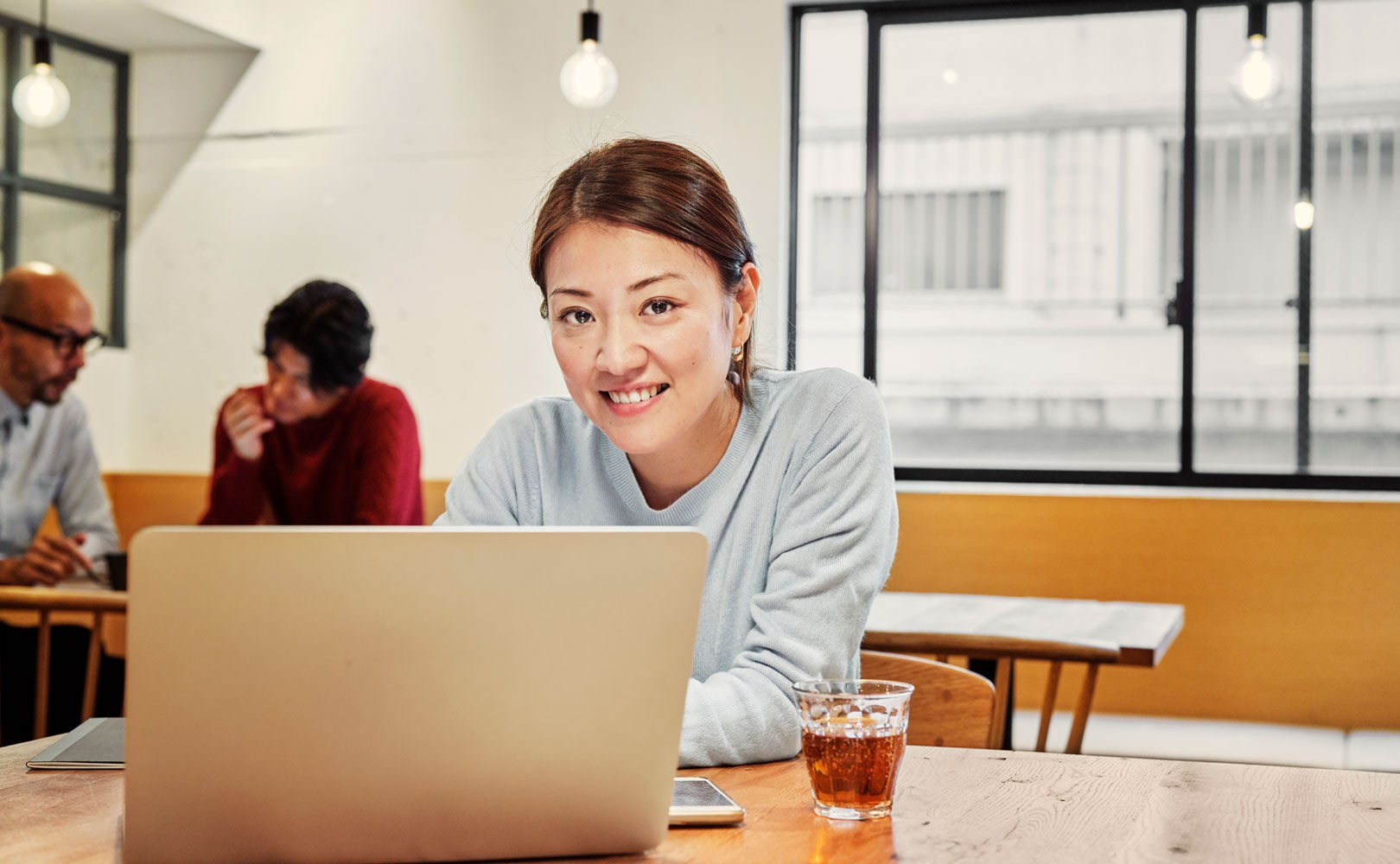 Photo of woman sitting behind laptop and smiling at camera