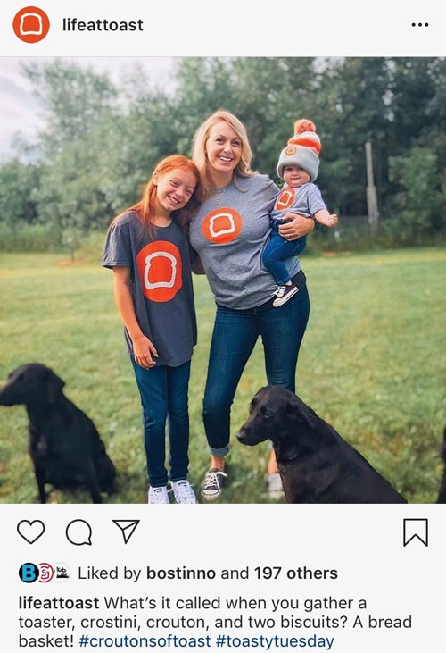 "Screenshot of posting on Toast's ""Lifeattoast"" Instagram account.  Photo is of woman and her two children and two dogs.  Social copy: What's it called when you gather a toaster, crostini, crouton, and two biscuits? A bread basket! #croutonsoftoast #toastytuesday"