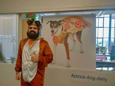 Photo of man in dog costume in front of painting of dog in pizza cape above the hashtag: #pizza-dog-daily