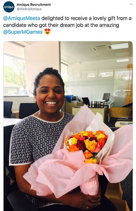 Screenshot of tweet from Amiqus Recruitment (@WeAreAmiqus) with photo of recruiter holding bouquet of flowers wrapped in pink paper:  @AmiqusMeeta delighted to receive a lovely gift from a candidate who got their dream job at the amazing @SuperMGames
