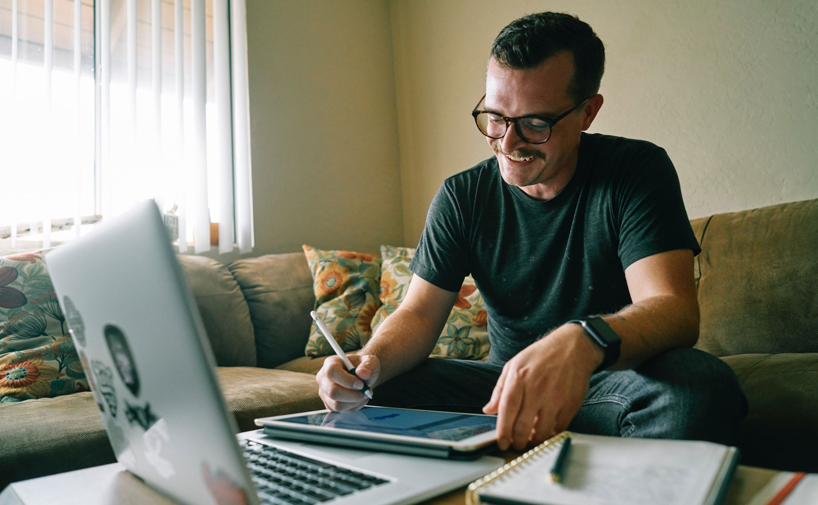 Photo of man working from home on his couch
