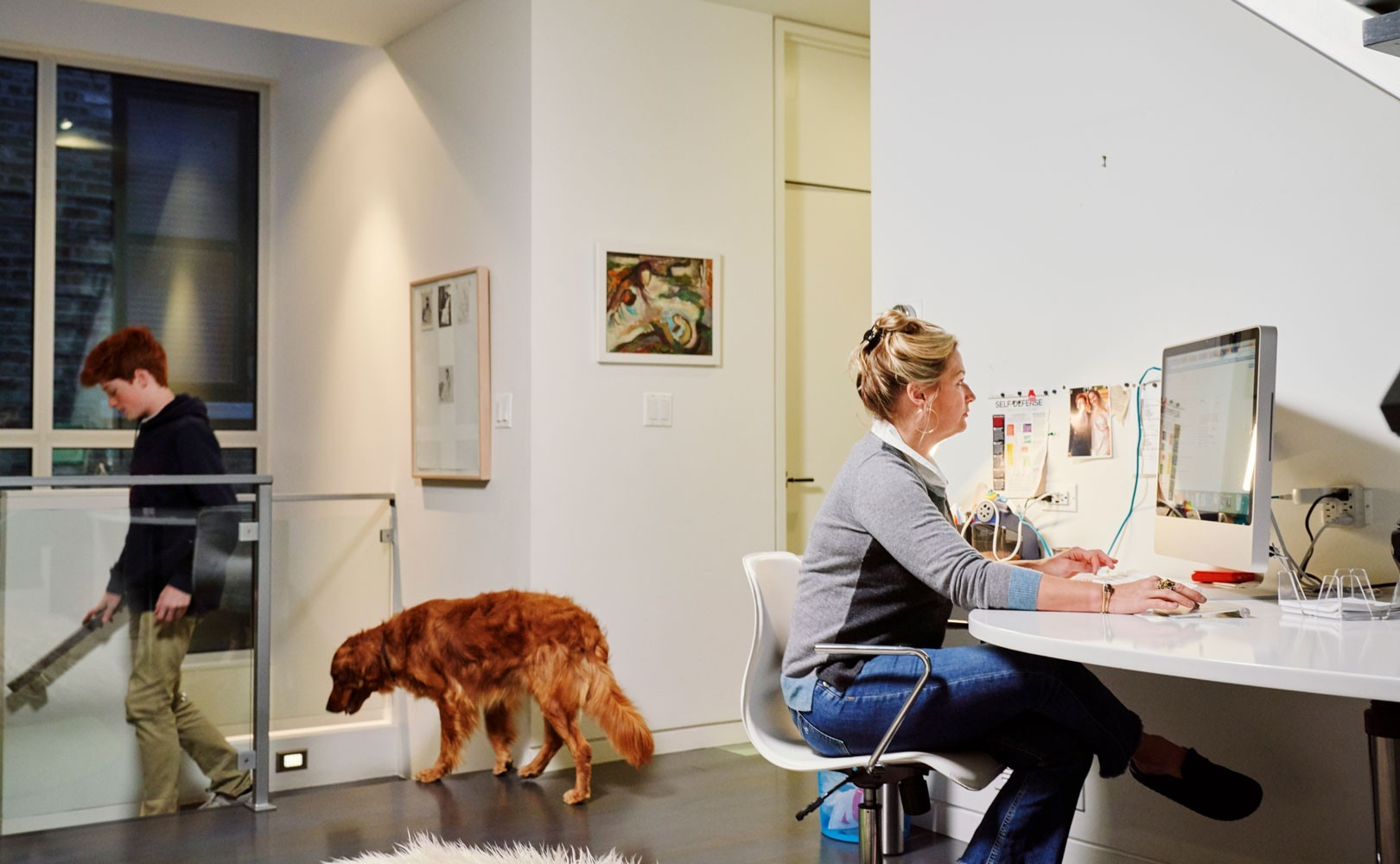 Photo of woman working from home with dog and child in background