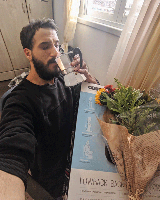 Photograph of new Soluto employee with the welcome gifts sent to all new employees, including espresso pot, lumbar support product to add to your chair, and a bouquet of flowers.