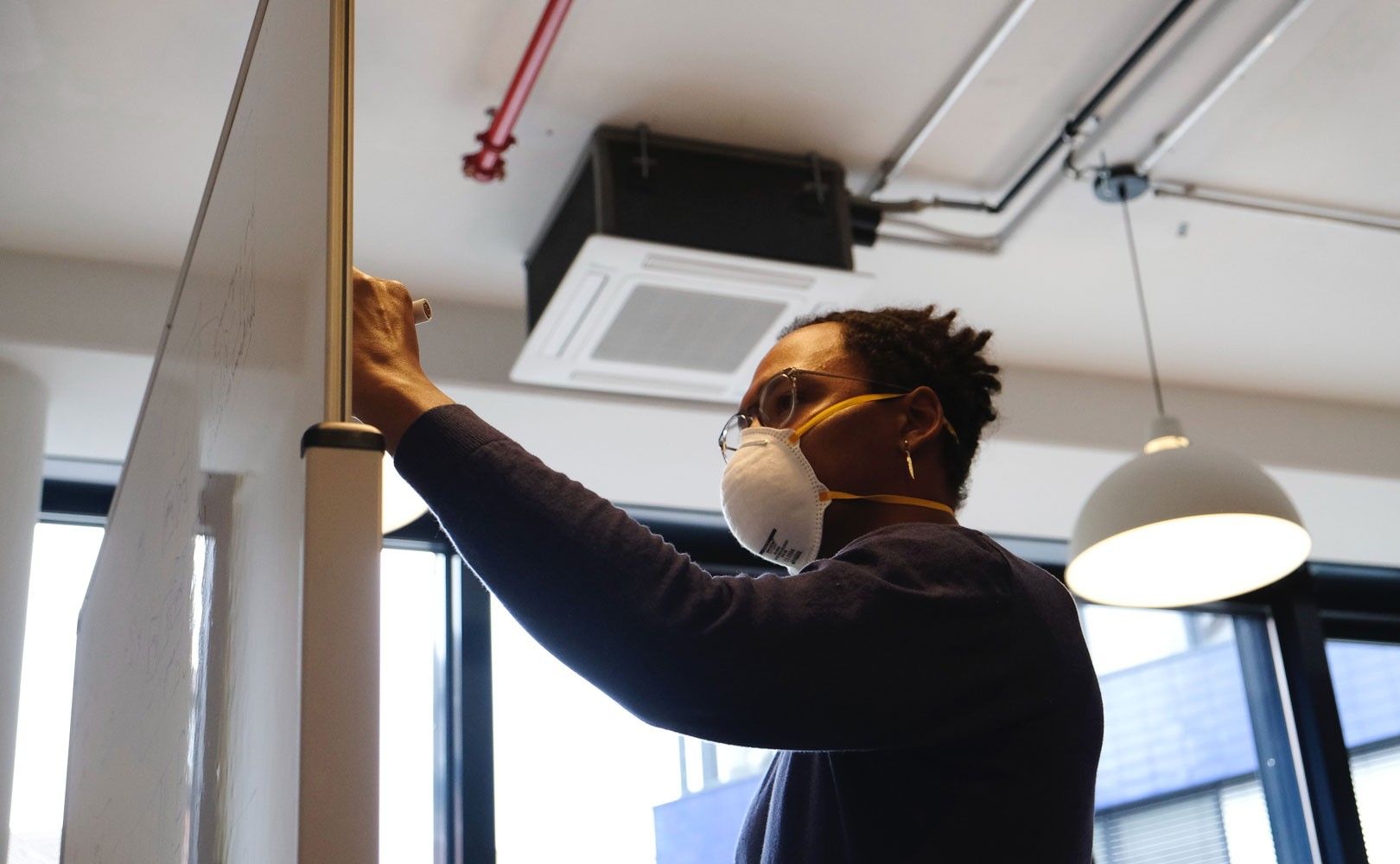 Photo of person wearing face mask writing on white board in office