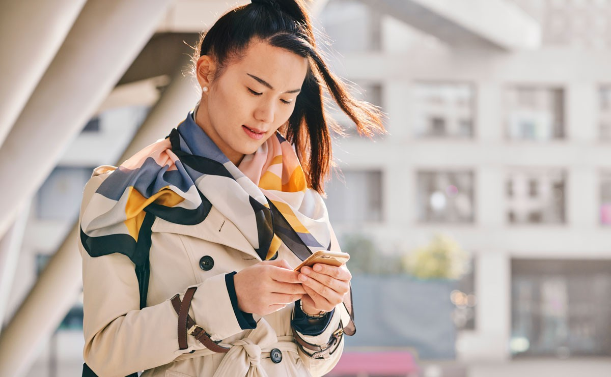 Woman standing outside looking at her phone