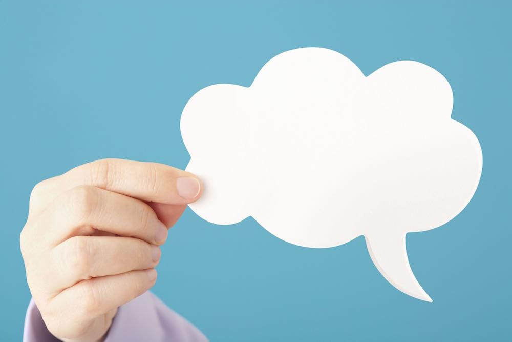 Hand holds blank cloud shaped speech bubble